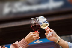 Two people clinking glasses with red and white wine. On blurred background. Man and woman cheers with alcohol drink closeup royalty free stock photos