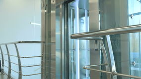 Two people coming out of elevator at the airport. The camera moves front to back. Handsome businessman wearing suit and beautiful woman come out of elevator stock footage