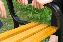 Two people constructing bench together. Two people constructing wooden and metal bench together in the grass stock photo