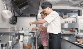 Two people cooking, commercial kitchen royalty free stock photography