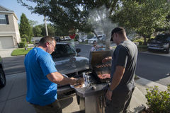 Two people cooking on an outside grill Royalty Free Stock Image