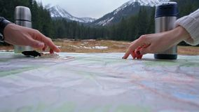 Two People are Discusiing the Hiking Route on a Map with Compass by Fingers. Two People are Discusiing the Hiking Route on a Map with Compass by Pointing Fingers stock footage