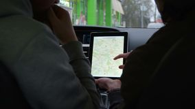Two people discuss the route in tablet with map in modern car. Shoot with RED EPIC stock video footage