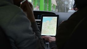 Two people discuss the route in tablet with map in modern car and start moving. Shoot with RED EPIC stock video