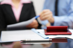 Two people discussing about report on business meeting with focus on pen.  royalty free stock image
