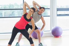 Two people doing power fitness exercise at yoga class Stock Photos