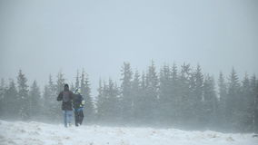 Two people down from the mountains in a blizzard stock footage