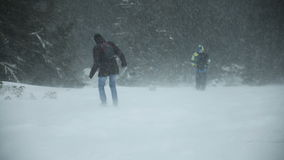 Two people down from the mountains in a blizzard. Shot of two people down from the mountains in a blizzard stock video