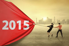 Two people drag number 2015 for a change Stock Image