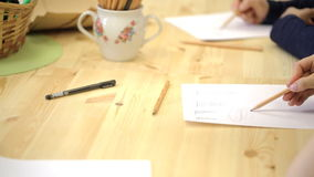 Two people draw vortices by pencil on paper on nice wooden table. On new unpainted wooden desk there is sugar bowl like vase full of pencils. Nearby lie one stock footage
