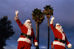 Two people dressed as Santa. These are two people dressed as Santa next to palm trees. It shows that Santa Claus is in California at Christmastime Stock Photography