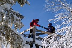 View from the mountain to the snow over the plain. Two people on an equipped trail in the winter mountains; the men holds out his hand to the woman, helping to royalty free stock image