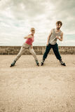 Two people exercise stretch outdoor on rollerblades. Stock Photos