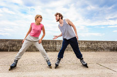 Two people exercise stretch outdoor on rollerblades. Royalty Free Stock Photos