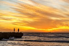 Two fisherman on a rock at sunset