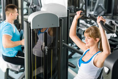 Two people at fitness center exercise machine Royalty Free Stock Image