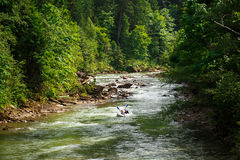 Two people floating in a canoe on a mountain river Stock Photos