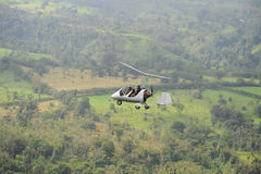 Two people flying in autogyro. Autogyro flying above the tropical landscape in Costa Rica Stock Image