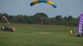 Two people flying on a parachute at blue sky and landing on green grass of airport stock video footage