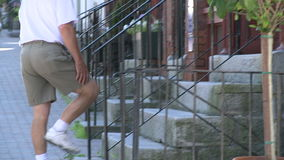 Two people going up stone steps on brick building stock video