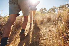 Two people going uphill on a mountain trail Royalty Free Stock Photo
