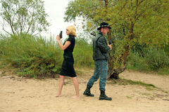Two people with guns, duel. Man in hat and blond women with guns, duel Stock Image