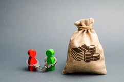 Two people are handcuffed to each other and stand near a money bag. Unclosed obligations between two persons, financial or moral. Debt. refusal to return debts stock image