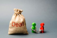 Two people are handcuffed to each other and stand next to the bag labeled Deal. Unclosed obligations between two persons. Financial or moral debt. refusal to royalty free stock photo