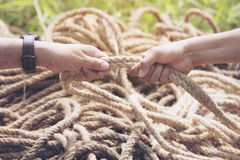 Two people hands pulling the rope.  royalty free stock images