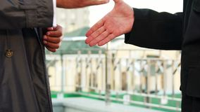 Two people handshake. Two people stand facing each other. They are dressed in official style clothes. Close-up of the show of how they shake hands stock footage