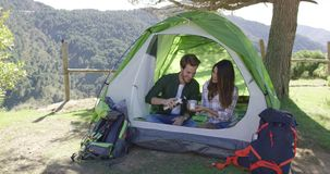 Two people having rest in tent. Young laughing couple sitting in tent and drinking tea while taking rest in mountains stock video