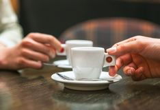 Free Two People Holding Cups Of Coffee Sitting In Cafeteria. Royalty Free Stock Photo - 116931855