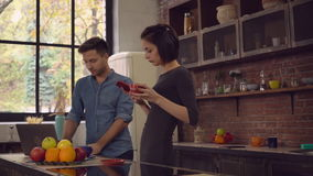 Two people holding cups and use gadgets indoors. Young business partners in startup working at home. Beautiful woman using smartphone and drinking coffee from stock video footage