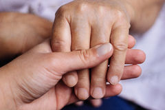 Two people holding each other's hands Stock Image