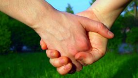 Two people holding hands. On green grass background stock footage