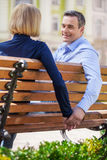 Two people holding hands while sitting on bench. Royalty Free Stock Image