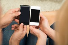 Two People Holding Mobile Phones Royalty Free Stock Photos