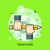 Two people holding pencil together. Teamwork, business community support and corporate strategy concept Stock Photo