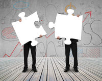 Two people holding puzzles to connect Stock Images