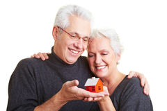 Two people holding a small house Stock Image