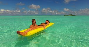 V13899 two 2 people inflatable sunbed romantic young people couple with drone aerial flying view on a tropical island of. Two 2 people inflatable sunbed romantic stock video