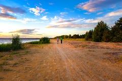 Two people jog along the coast. At sunset Stock Photos