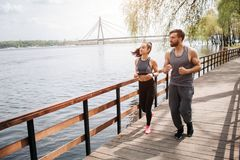 Two people are jogging on the bridge. There is a river nearby. Man and woman are looking at the river and running. stock image