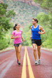 Two people jogging for fitness running on road Royalty Free Stock Photo