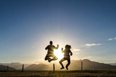 Silhouette couple jumping happy with backgroud sun and mountains stock photos