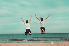 Two people jumping by the sea. Concept of fun on the beach. royalty free stock image
