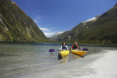 Two People Kayaking In Mountain Lake. Two young people kayaking in the lake with mountains in background stock photo