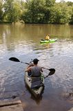 Two people in kayaks on a river in summer stock images