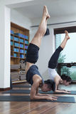 Two people with legs raised doing yoga in a yoga studio stock photo