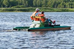 Two people in life jackets ride on an iron boat on the river, rear view royalty free stock photos